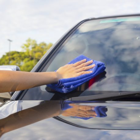 Women's hand wiping on car.